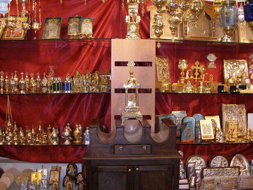 At the front there is a three-slot Candle Case and behind it various Icons, Oil Candles and Chalice Sets (Exhibition Laiki Texni 2009).